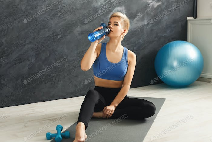 Fitness woman drinking water at gym on grey background