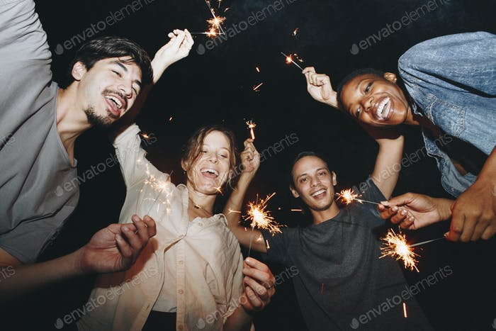 Mixed Race Freunde spielen mit Wunderkerfeier und festlichem Party-Konzept