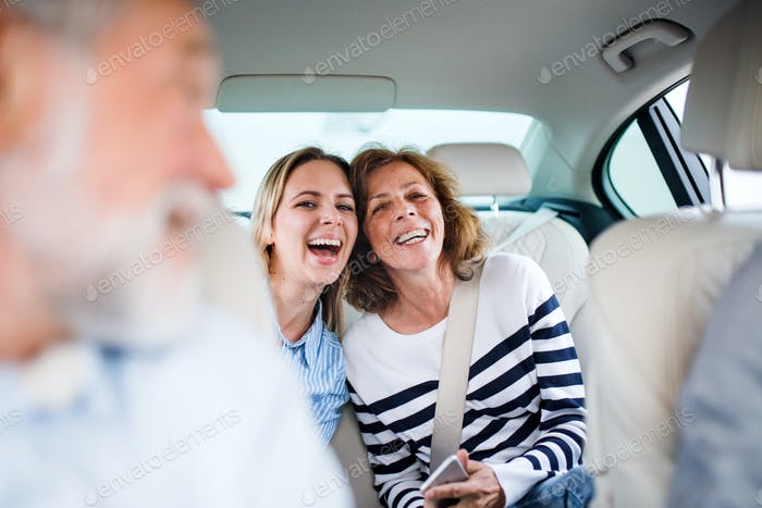 Cheerful adults sitting in car, going on a trip