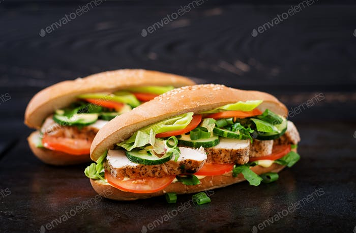 Big sandwich with chicken breasts, tomato, cucumber and herbs.