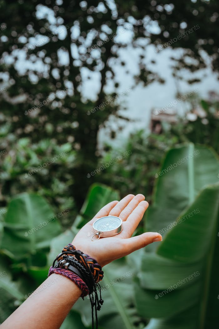 Hand with compass in the lush rainforest jungle