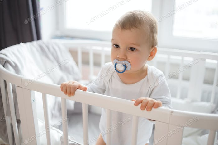 Cute baby boy standing in white round bed.