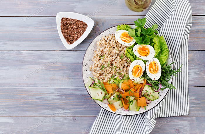 Breakfast bowl with oatmeal, zucchini, lettuce, carrot and boiled egg. Fresh salad. Healthy food