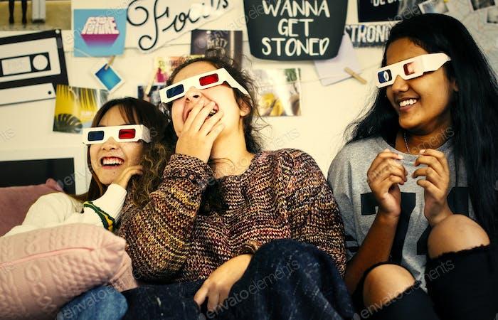 Teenage girls wearing 3d movie eyeglasses enjoying laughing and