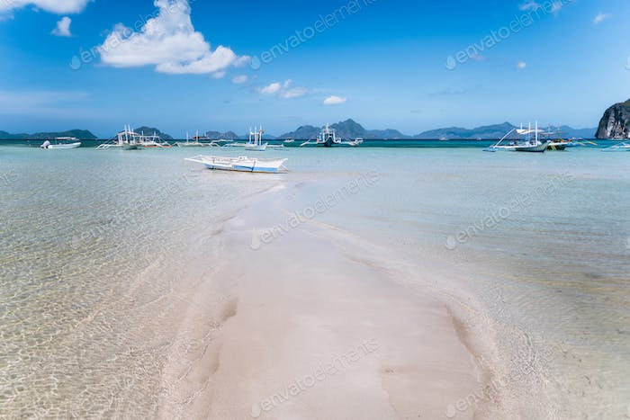 El Nido, Palawan, Philippines. Tropical scenery of banca boat on the sandy beach in low tide