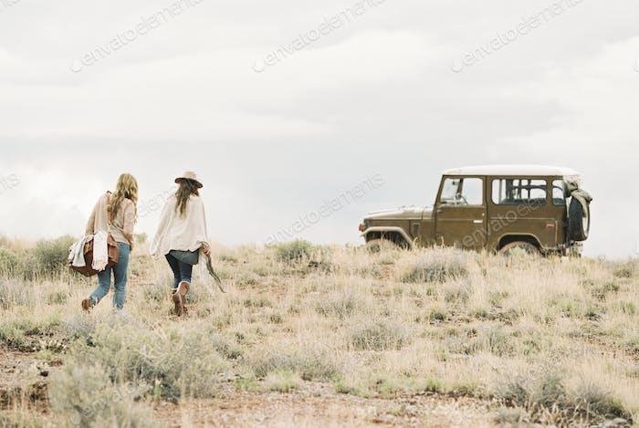 Two women walking towards a 4x4 vehicle in an open space.