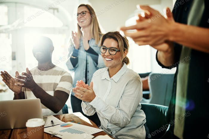 Smiling group of diverse office colleagues clapping during a meeting