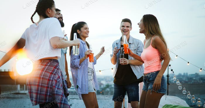 Friends enjoying cocktails at a party. Group of happy people having fun, dancing on a rooftop