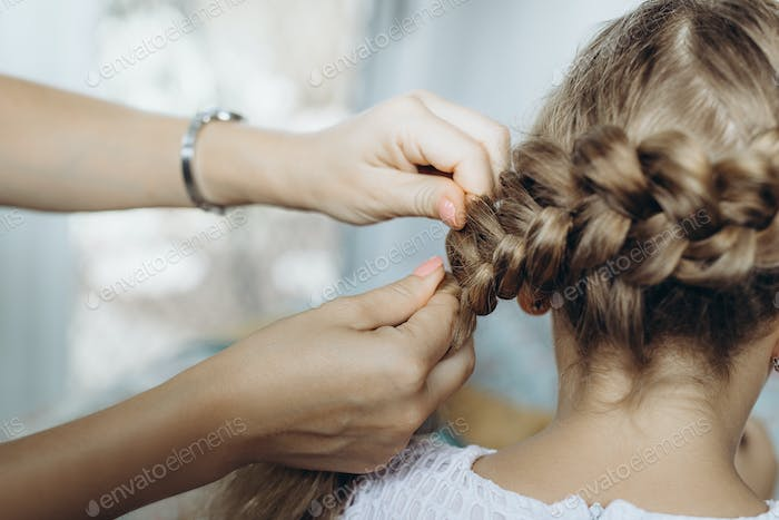 Mother do hair braid to her daughter