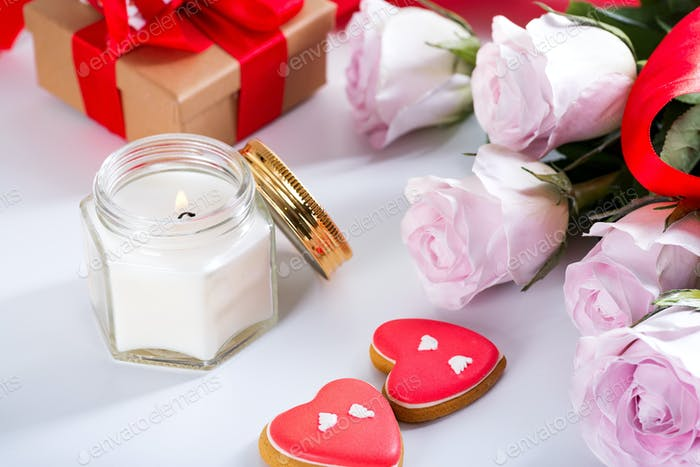 Homemade Valentines day heart cookies, pink roses and candle on white table , copy space