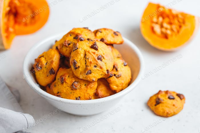 Pumpkin cookies with chocolate chips made from cake mix in a white ceramic bowl.