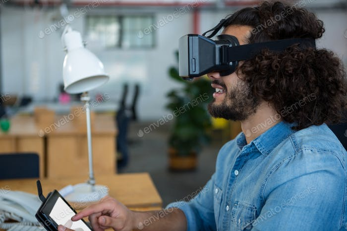 Graphic designer using the virtual reality headset and digital tablet