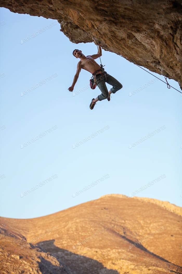 Male rock climber hanging with one hand on cliff
