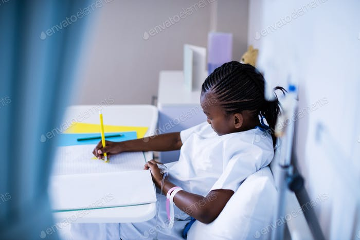 Patient writing on the book while sitting at hospital