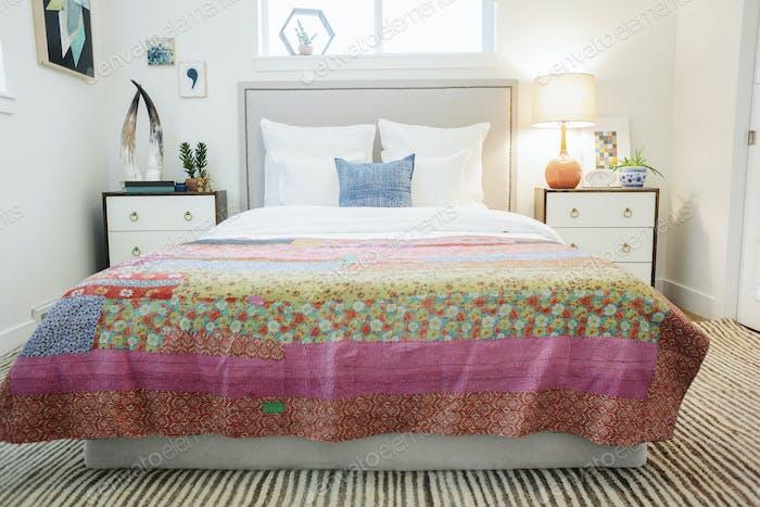 Doppelbett mit Patchwork-Steppdecke