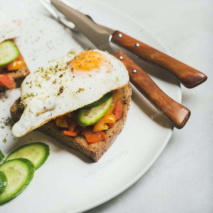 Breakfast toast with fried eggs, vegetables. square crop