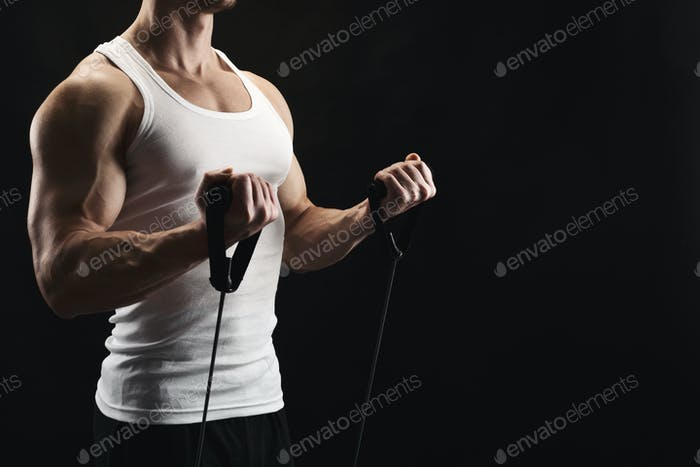 Athletic muscular man exercising with elastic expander at black