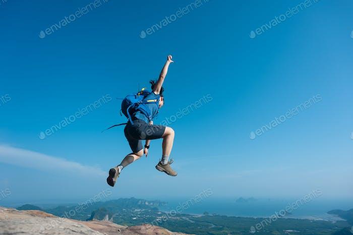 Suitoso excursionista saltando en la cima del acantilado de la montaña