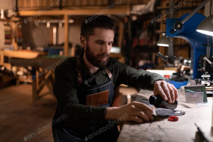 Male artisan poring leather glue over workbench
