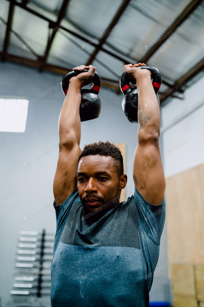 Athletic man doing exercise with crossfit kettlebel.