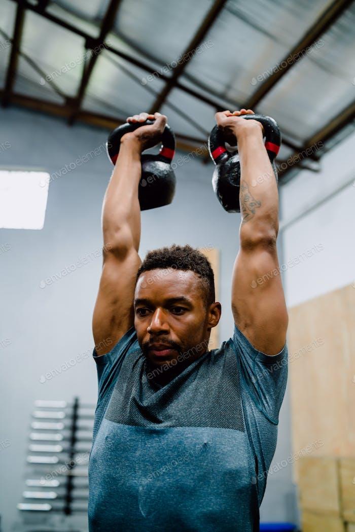 Hombre atlético haciendo ejercicio con crossfit kettlebel.