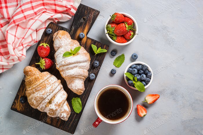 Croissant with fresh berries and cup of coffee