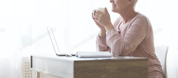 Senior lady holding cup of tea, sitting at workstation