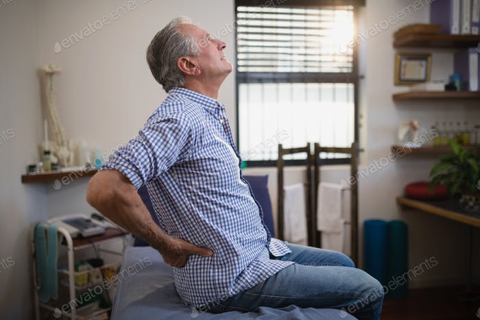 Side view of senior male patient suffering from back ache while looking up on bed
