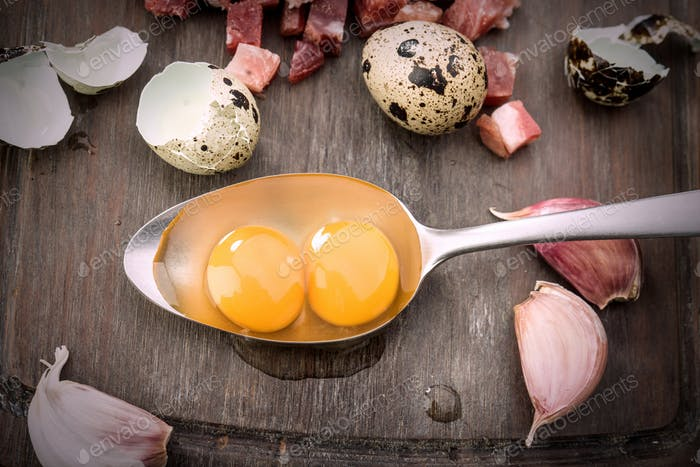 overhead shot of raw eggs and open quail in metal spoon, on rustic wood