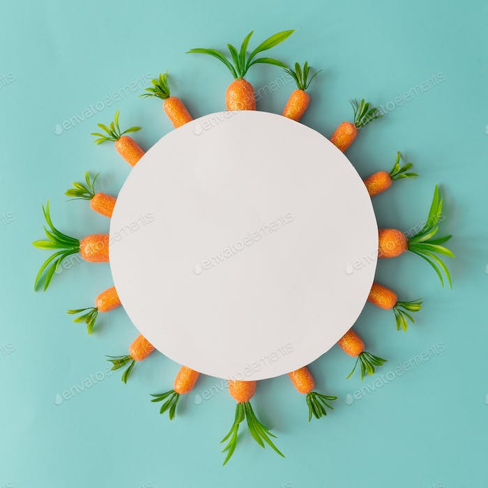 Creative composition made with carrots and paper card copy space. Minimal Easter holiday background.