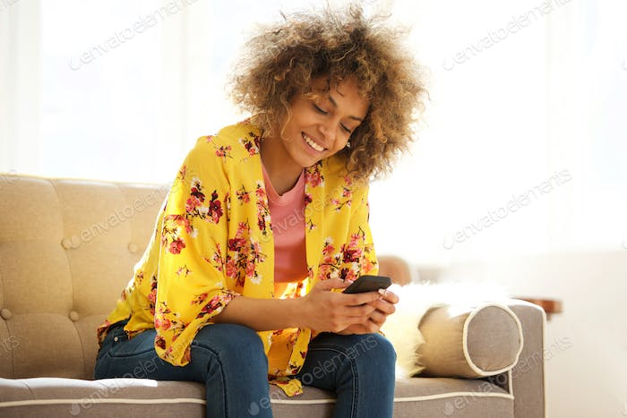 young woman sitting at home with mobile phone