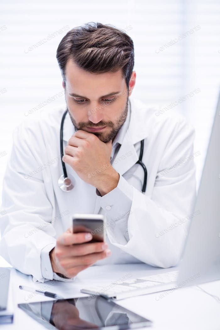Male doctor using mobile phone