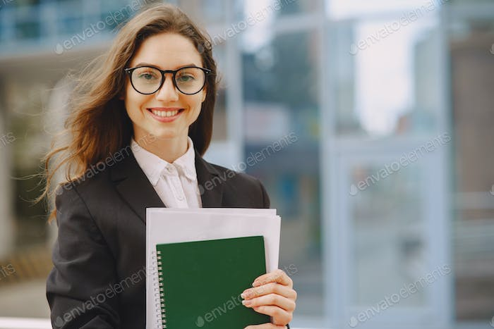 Businesswoman standing outdoors in city office building background