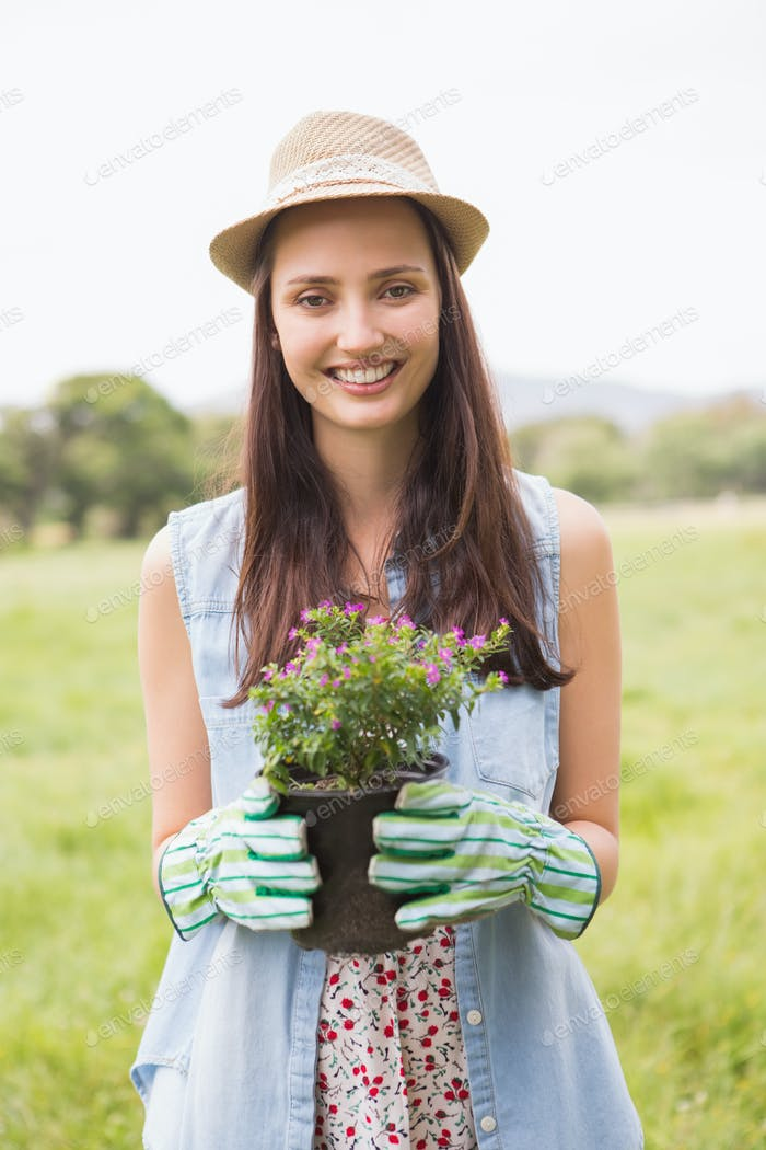 Happy woman holding potted flowers on a sunny day