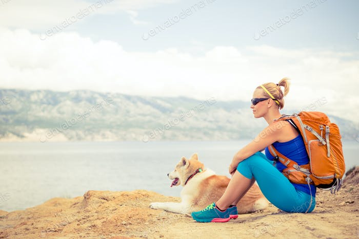 Woman hiking walking with dog on seaside trail