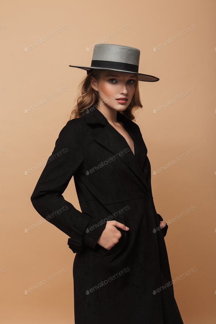 Young beautiful woman with wavy hair in black coat and hat thoughtfully looking in camera