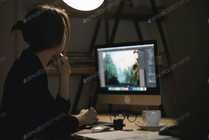 Concentrated young lady designer at night using computer