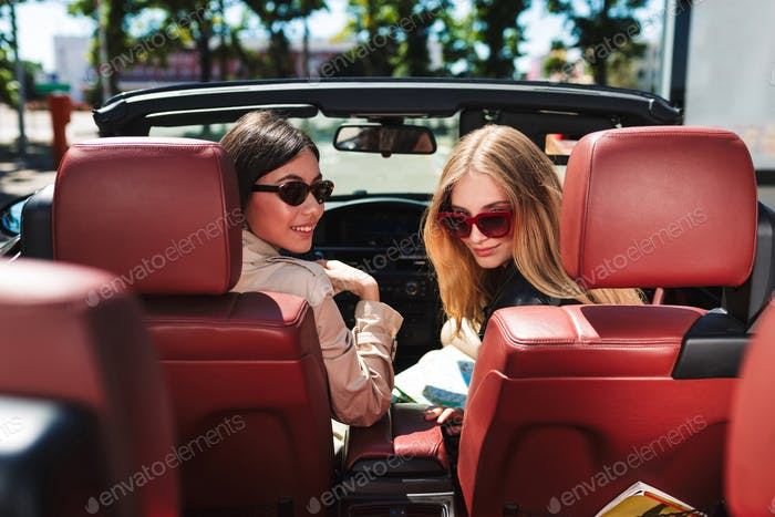 Beautiful girls in sunglasses happily looking in camera spending