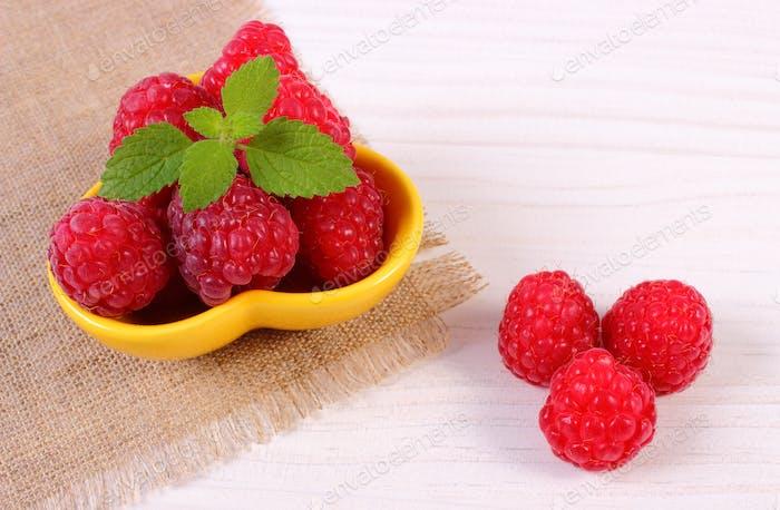 Fresh raspberries and lemon balm on white wooden board, healthy food and dessert