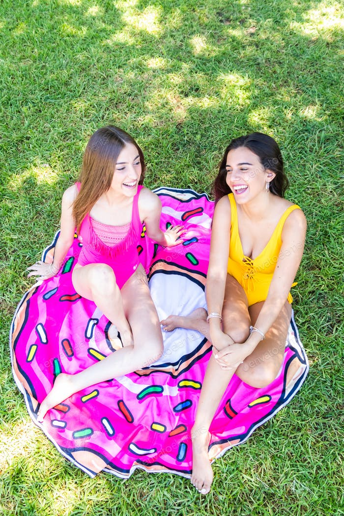 two teenage girls in a swimsuit sitting on the grass in the pool talking and laughing