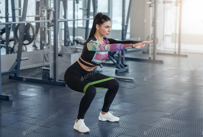 Motivated young girl doing squats with elastic band in sports club