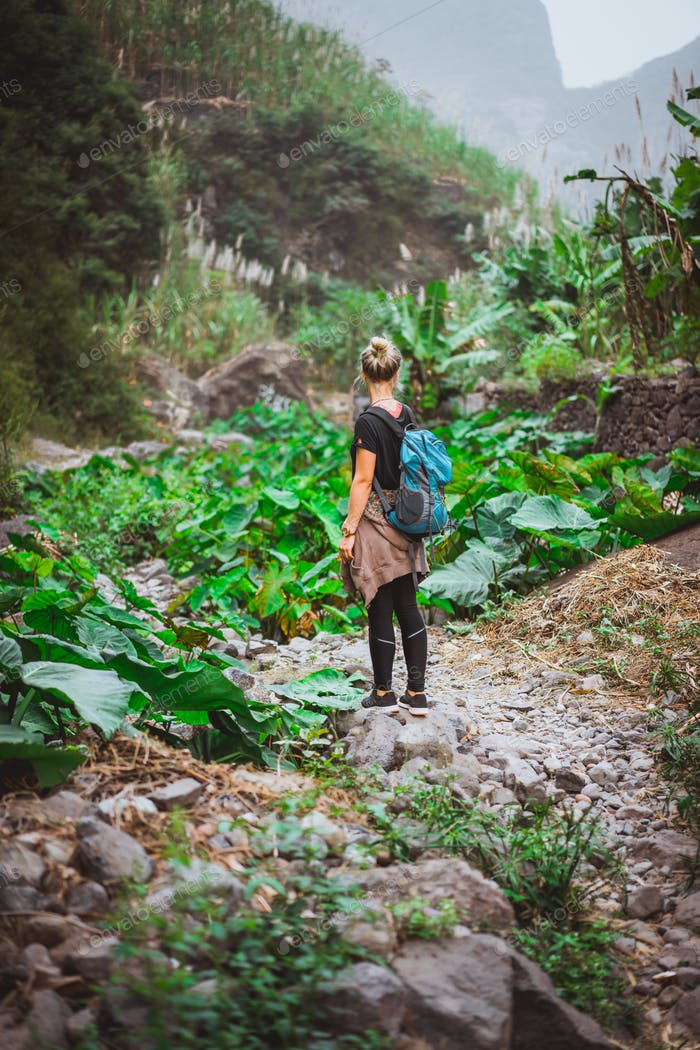 Girl admire the lotus plants on her way in lush green valley of the mountains. Santo Antao. Cape