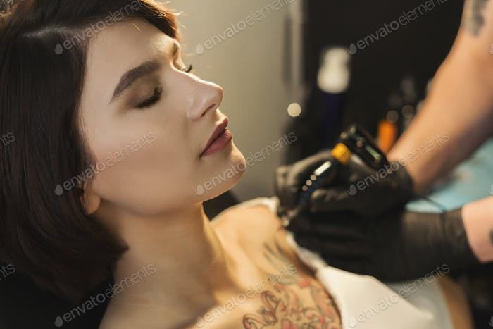 Tattoo artist working with needle on clients body