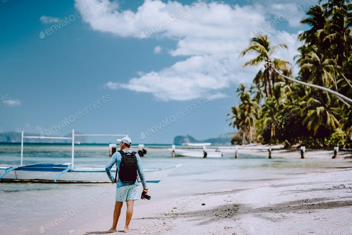 Back view of the man photographer with camera on pristine beach. Travelling tour most beautiful