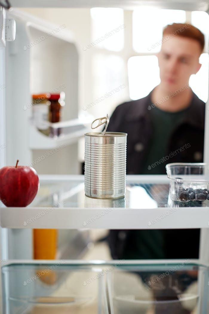 Junger Mann Blick in den Kühlschrank leer außer für offene Blechdose auf Regal