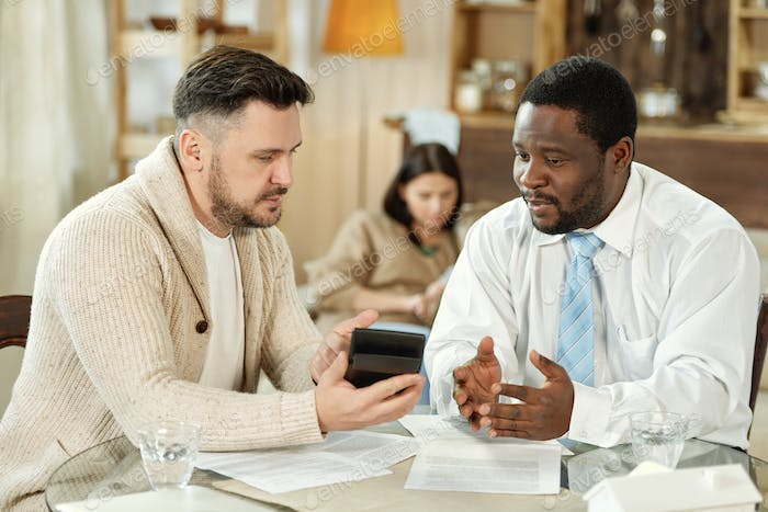Diverse men calculating home loan on consultation