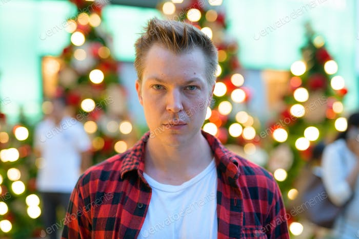 Face Of Young Handsome Hipster Man Against Christmas Trees Outdoors