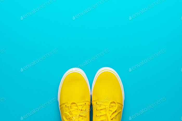 Pair Of Yellow Sneakers On Turquoise Blue Background With Copy Space
