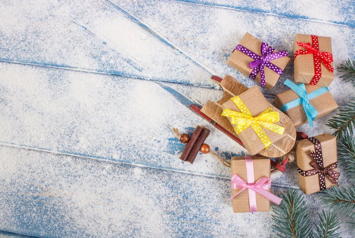Spruce branches and wooden sled with wrapped gifts for Christmas, copy space for text