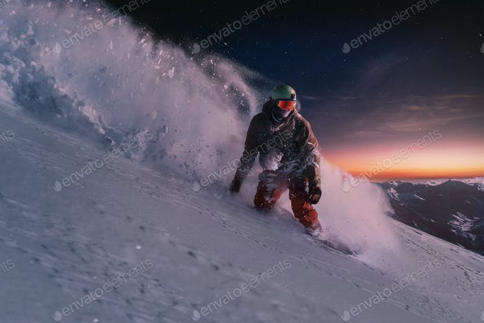 night skating snowboarder brakes spraying snow on freeride slope under starry sky and sunset light